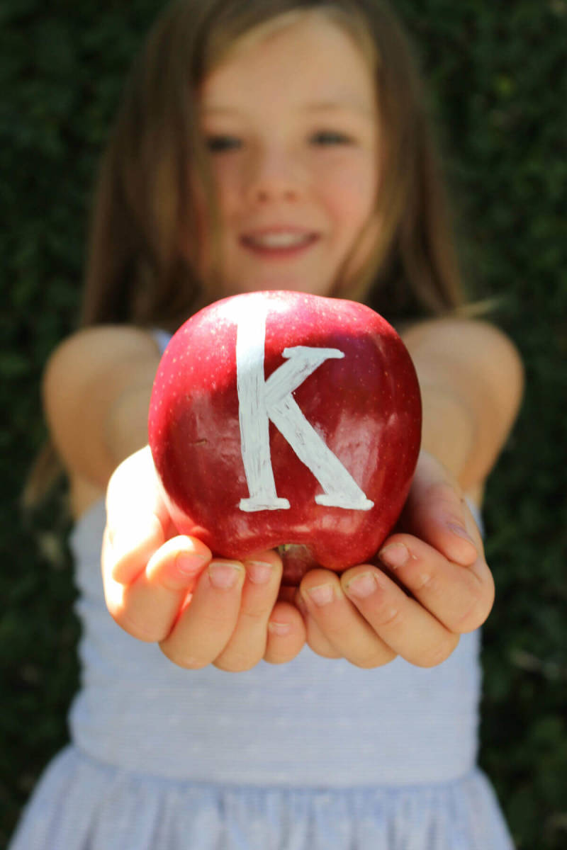 Incorporate simple props like pencils and apples into your back to school pics. Photo via Jane Can.