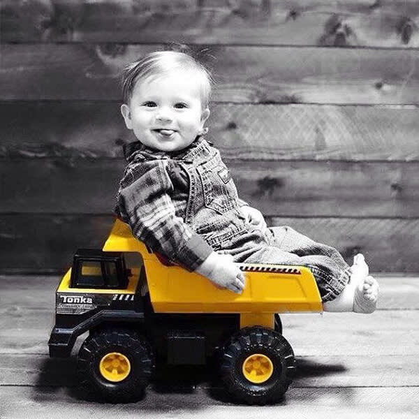 This black and white photo of a kid riding a Tonka truck gets kicked up a notch with a color pop.