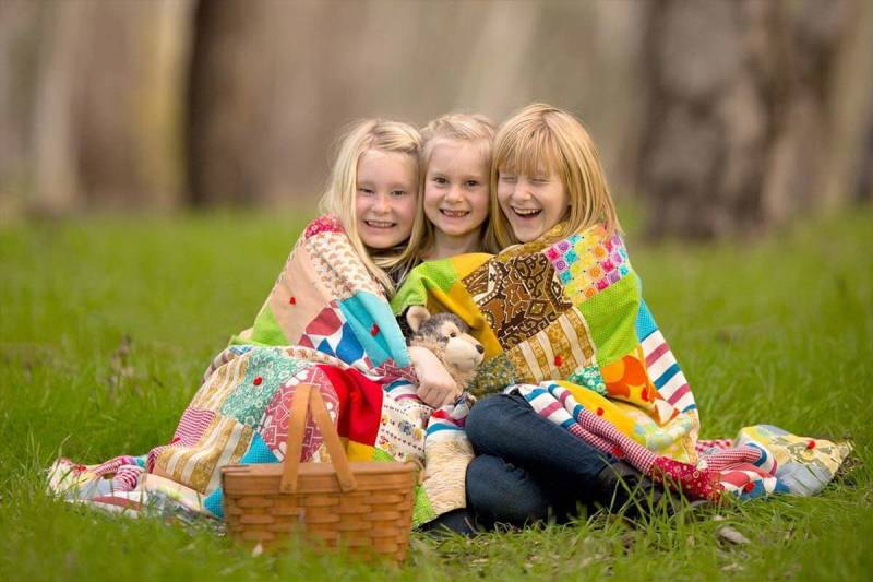 Photographer Erika Thornes shares tips for capturing joy, as seen in this photo of three siblings sharing a blanket.