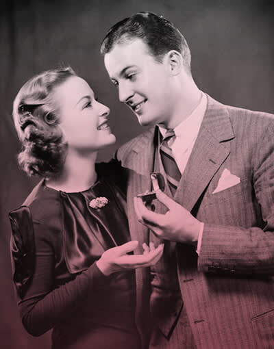 Old-school Valentine's Day: a 1940s guy holding a ring for his gal. Also, people being