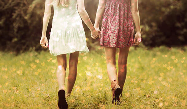 New-school Valentine's Day: two girls holding hands with Bokeh Hearts effect.