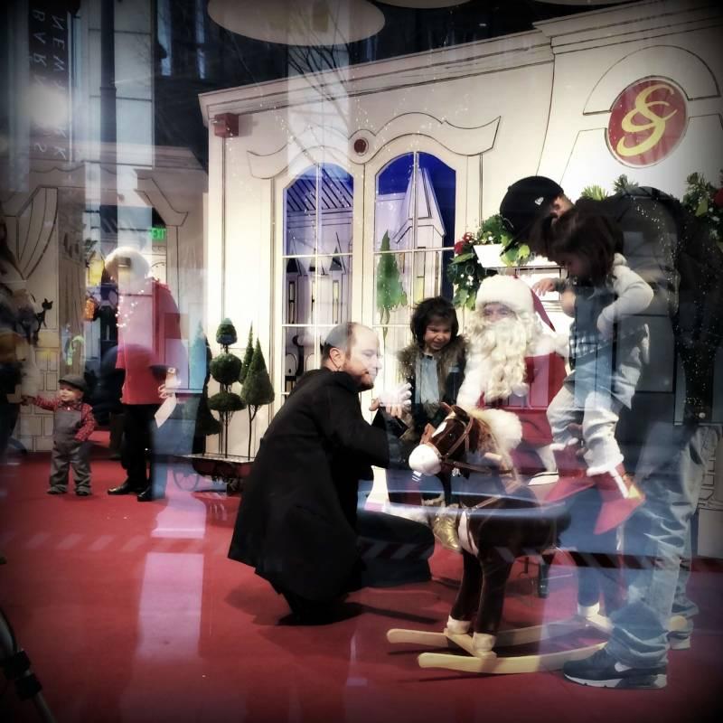 Photo walk: Santa greeting a child through a storefront window.