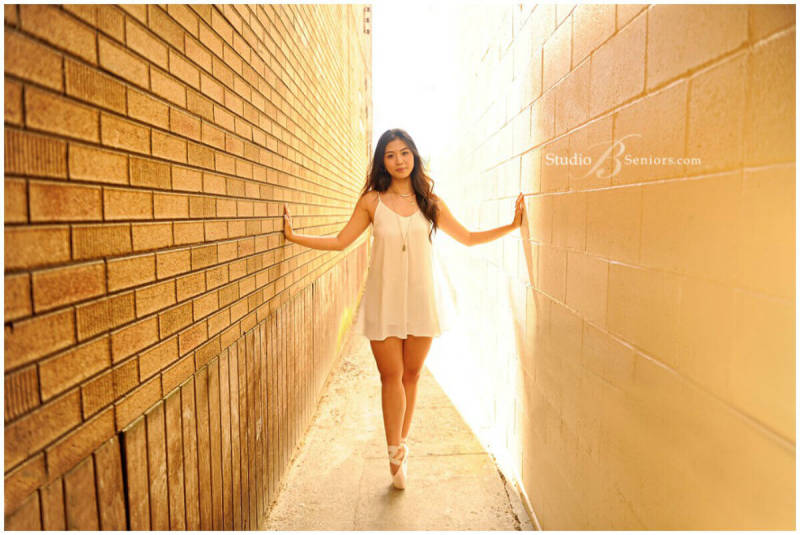 This portrait of a dark-haired girl en pointe in a sunlit alley shows that senior photos are especially effective when they highlight a grad's skills.