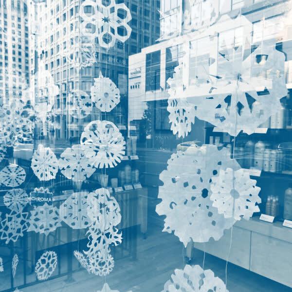 Staff photo walk: paper snowflake garland through a window storefront.