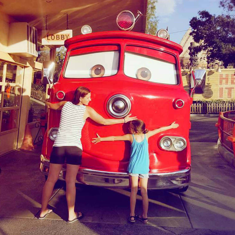 Mother and daughter hugging car at Cars Land at Disneyland