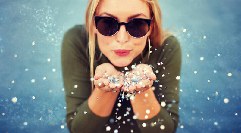 Use bokeh effects to play up image elements like this woman's handful of glitter.