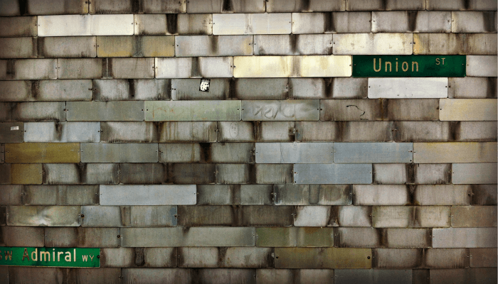 photo of a metal wall with street signs embedded