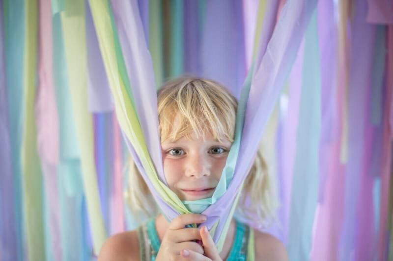 A blonde little girl stands amid a playful streamer photo backdrop, made from plastic tablecloths.