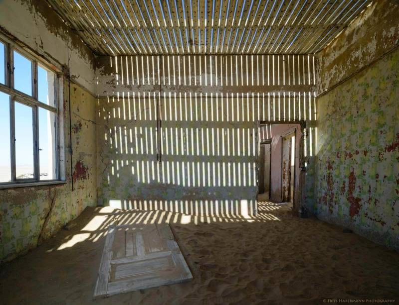 Exposed ceiling slats create light patterns inside this building in the Namibian ghost town of Kolmanskop.