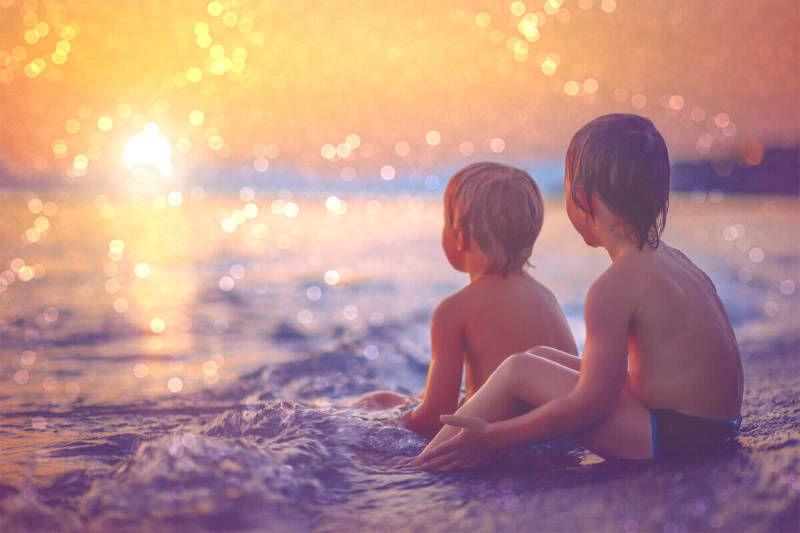 Bokeh effects can add interest to your backgrounds, as seen in this photo of two young boys watching a sunset on the beach.